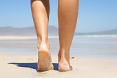 Woman walking barefoot on beach from behind