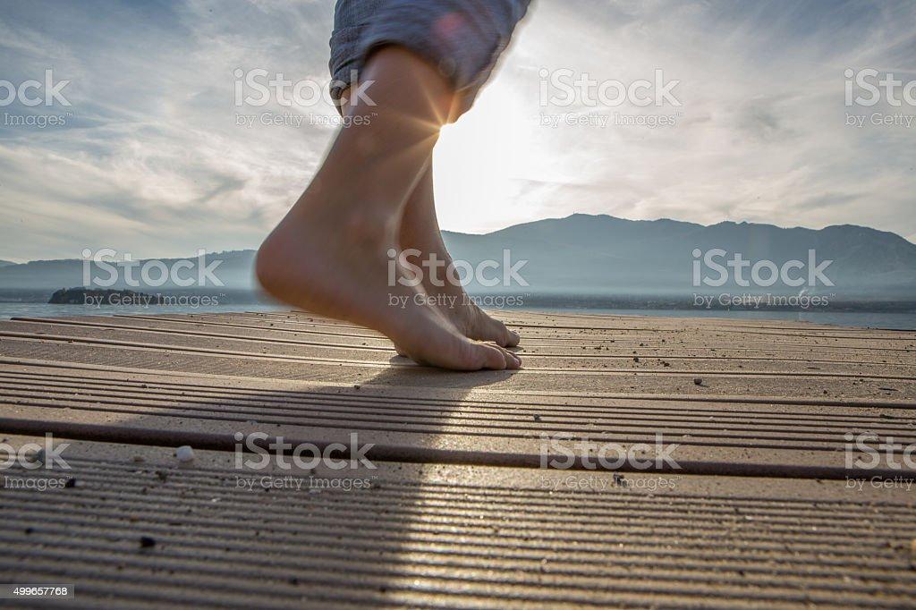 Woman walking barefoot on jetty above lake stock photo