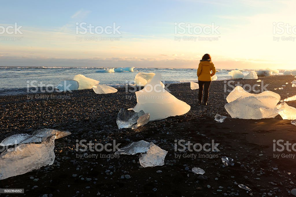 Woman Walking Between Icebergs on Lava Beach near Jokulsarlon Iceland stock photo