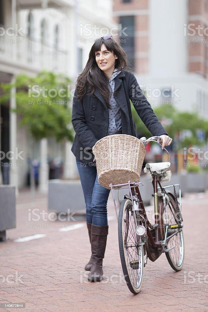 Woman walking bicycle on city street stock photo