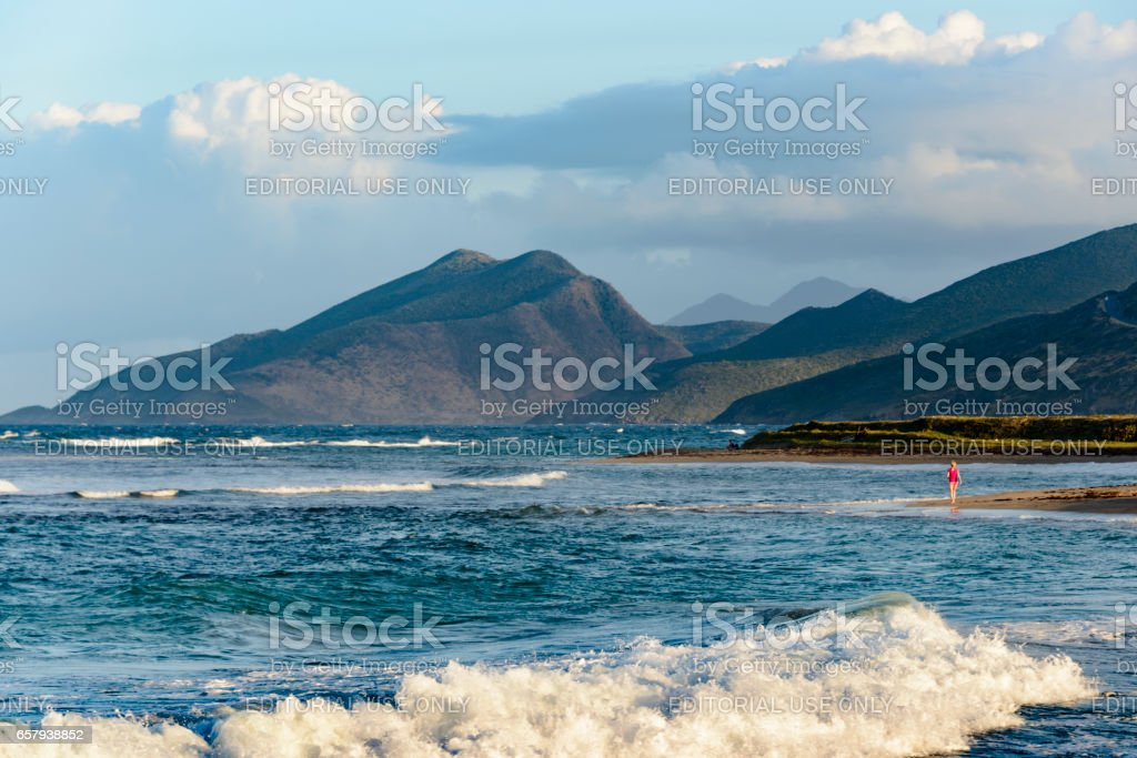 Woman walking by herself on a beautiful beach of a caribbean island stock photo