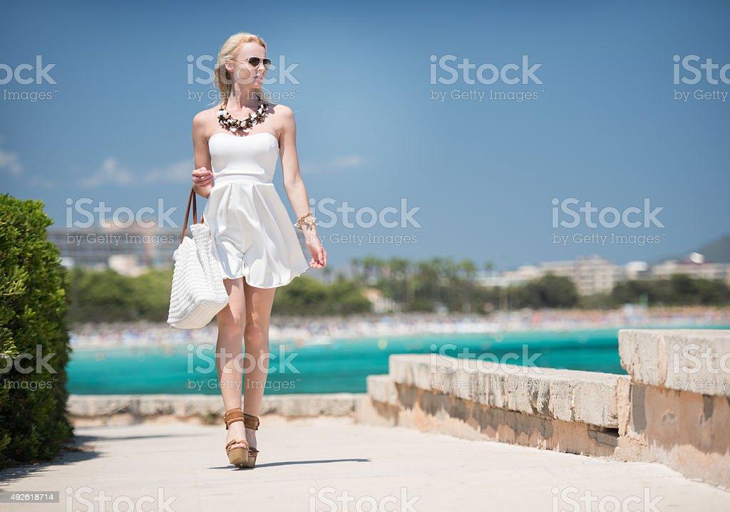Woman walking down a Beach Promenade stock photo