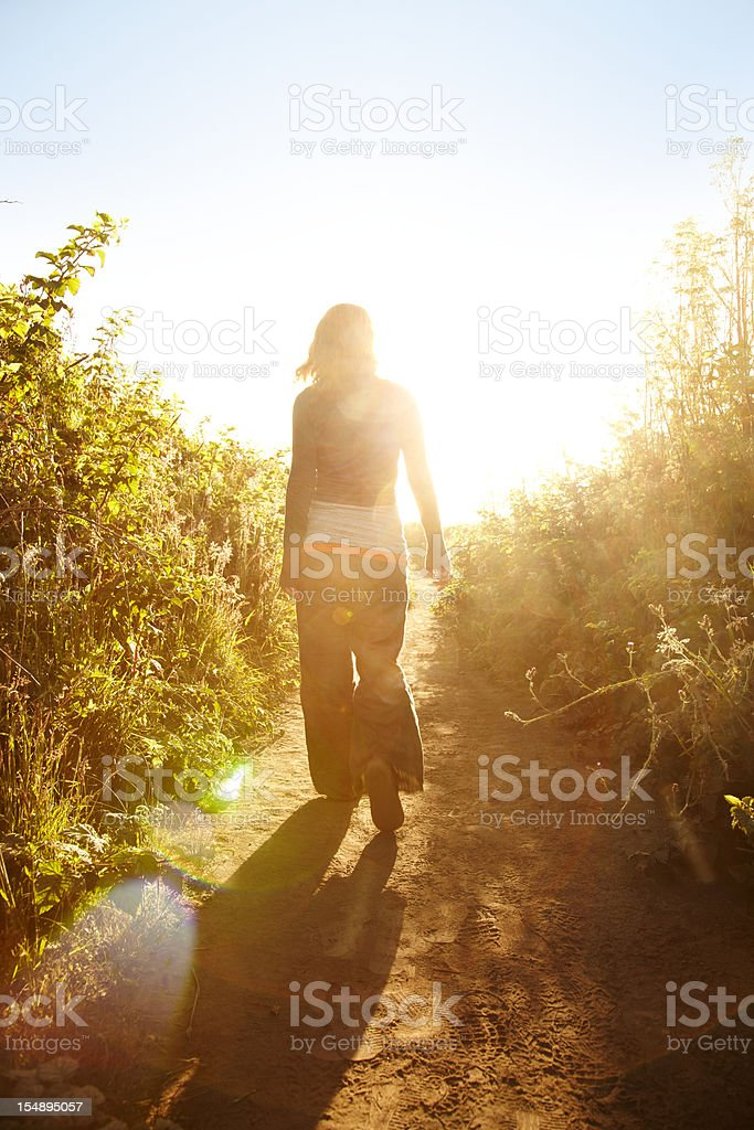 Woman walking down pathway in nature stock photo