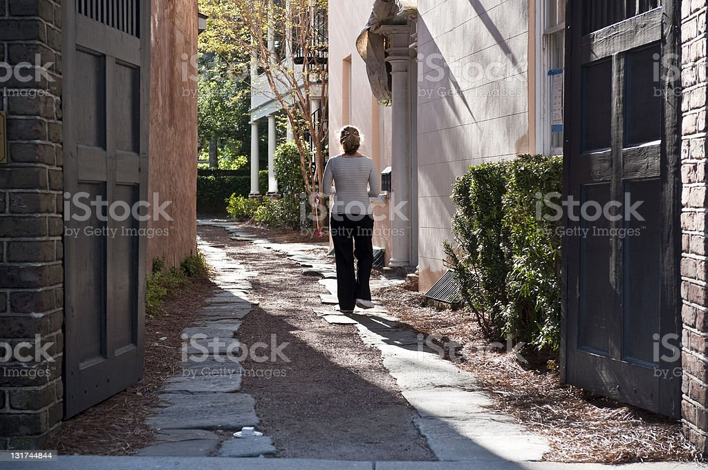 Woman walking in an alley royalty-free stock photo