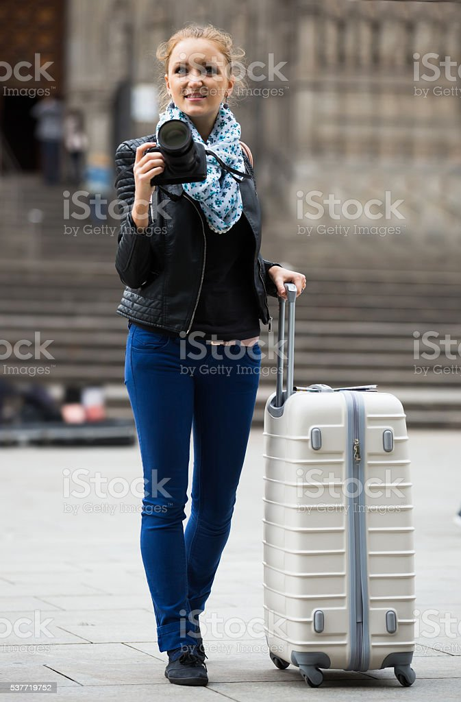 woman walking in autumn city with digital camera stock photo