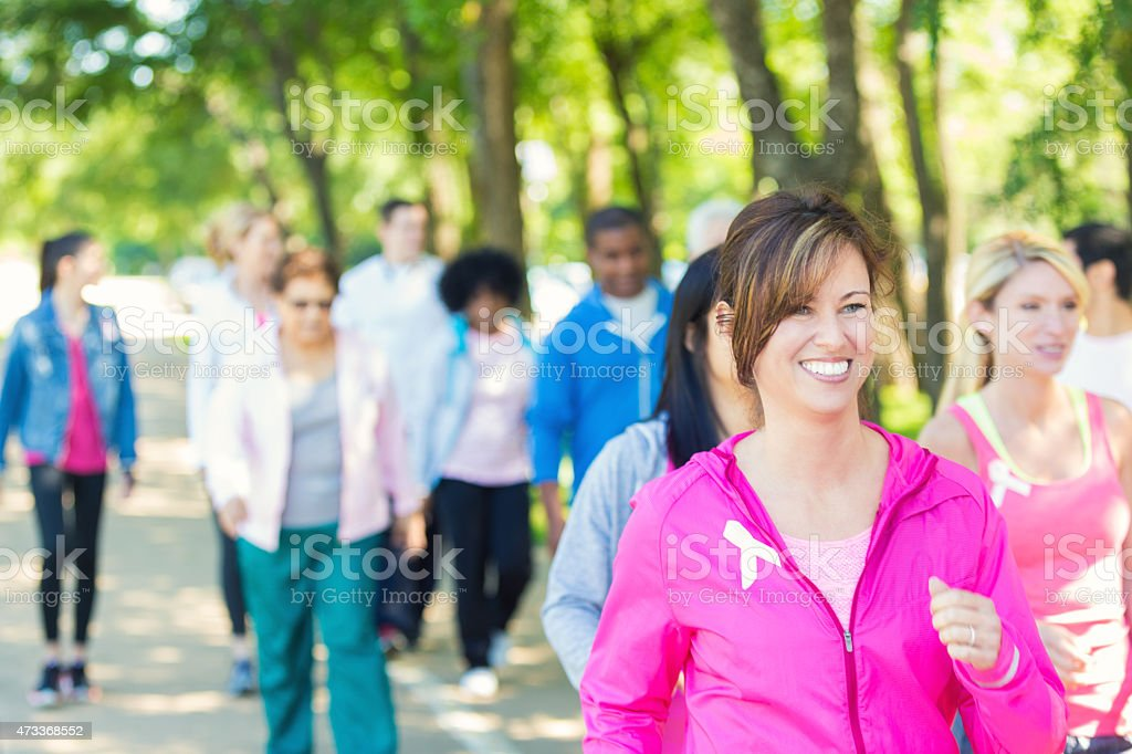 Woman walking in breast cancer awareness charity race event stock photo