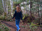 Woman walking in deep green forest in British Columbia