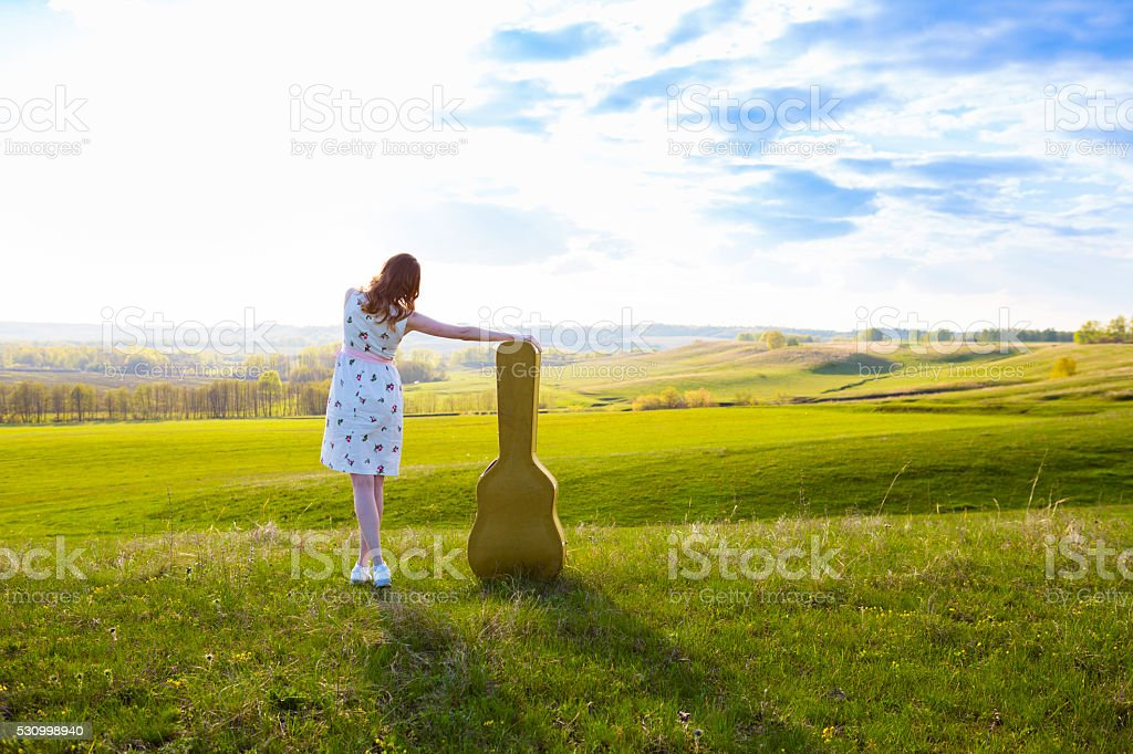 Woman walking in green field with acoustic Guitar stock photo