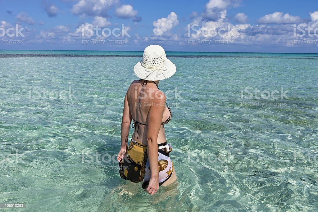 Woman Walking in Shallow Clear Water, Grand Cayman royalty-free stock photo