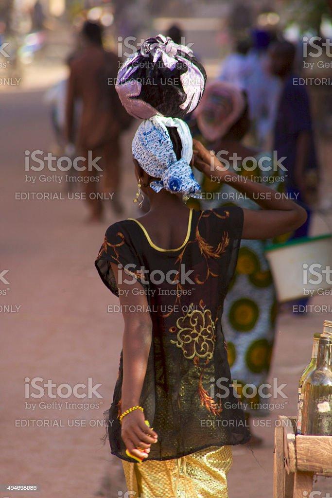 Woman walking in the busy street of Mopti, Mali stock photo