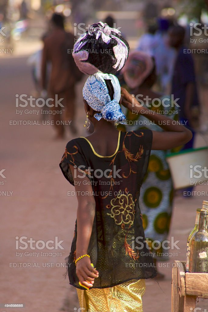 Woman walking in the busy street of Mopti, Mali stock photo