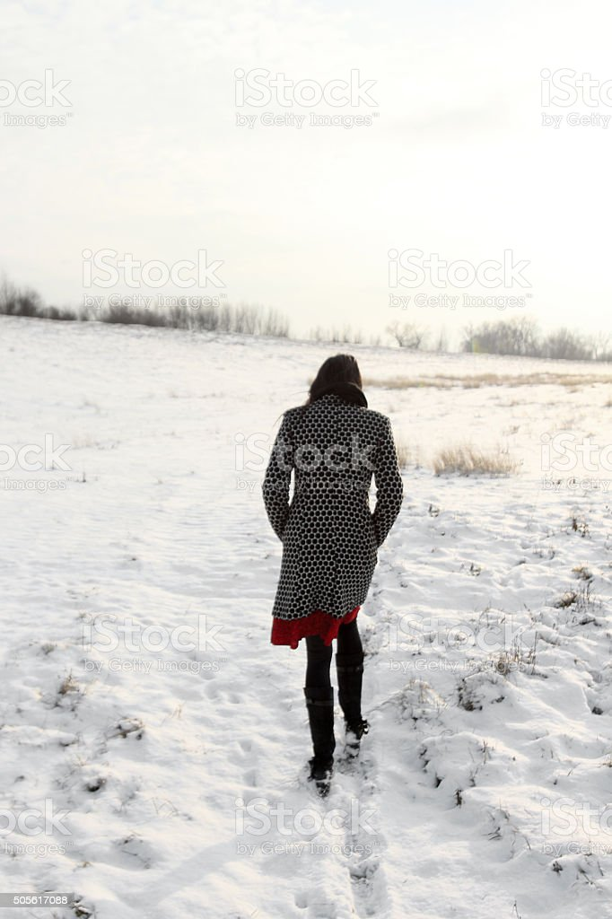 Woman walking in the snow stock photo