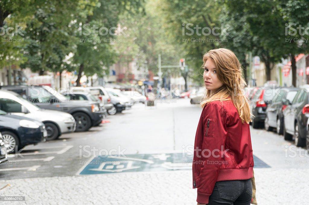 Woman walking in the street looking back stock photo