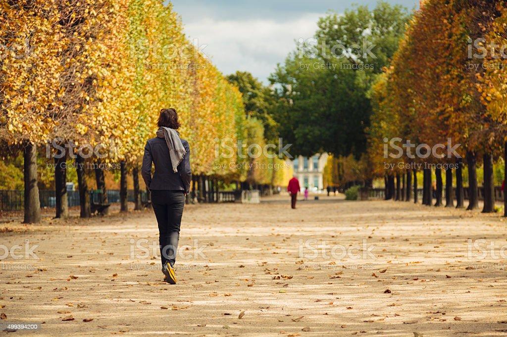 Woman walking in Tuileries Garden in Paris, France. stock photo