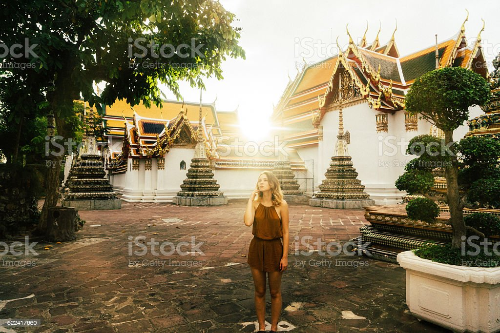 Woman walking in Wat Pho temple at sunrise stock photo