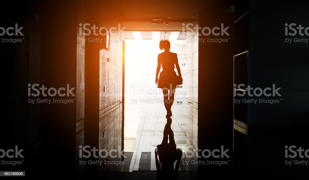 woman walking into the light stock photo