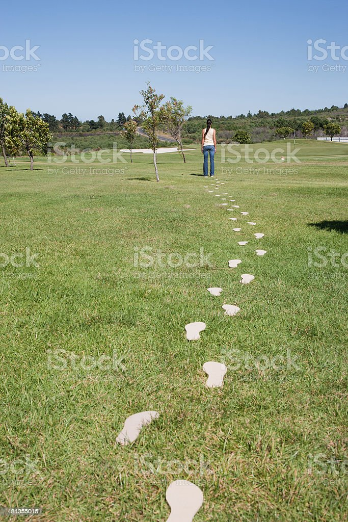 Woman walking leaving trail of footprints stock photo