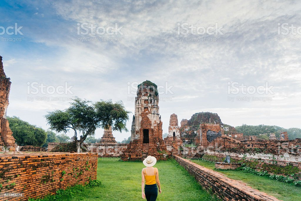 Woman walking near  ancient Buddhist Temple stock photo