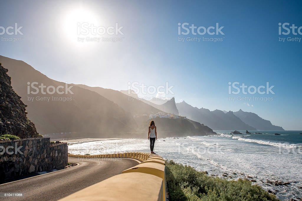 Woman walking near the mountain road stock photo