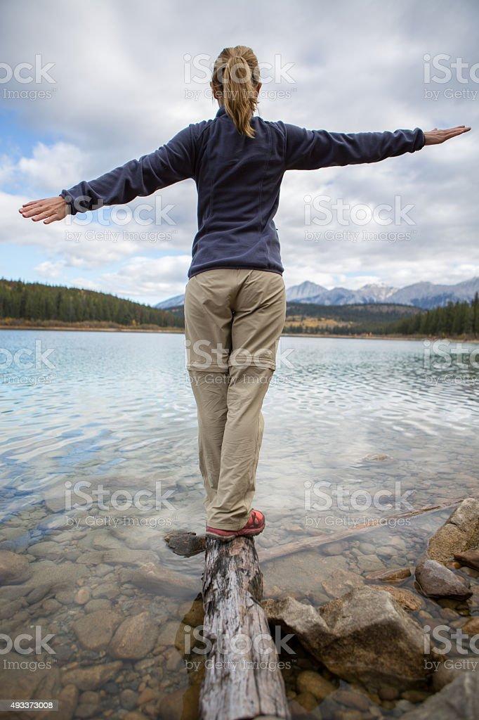 Woman walking on a tree log on the lake stock photo
