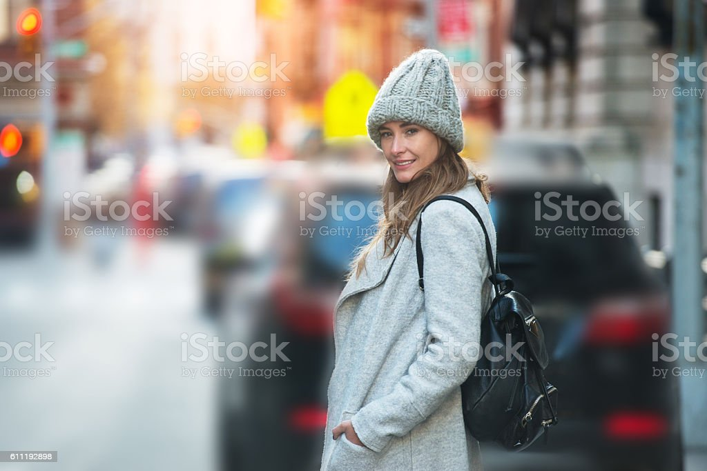 woman walking on city street wearing hat, jacket and backpack stock photo