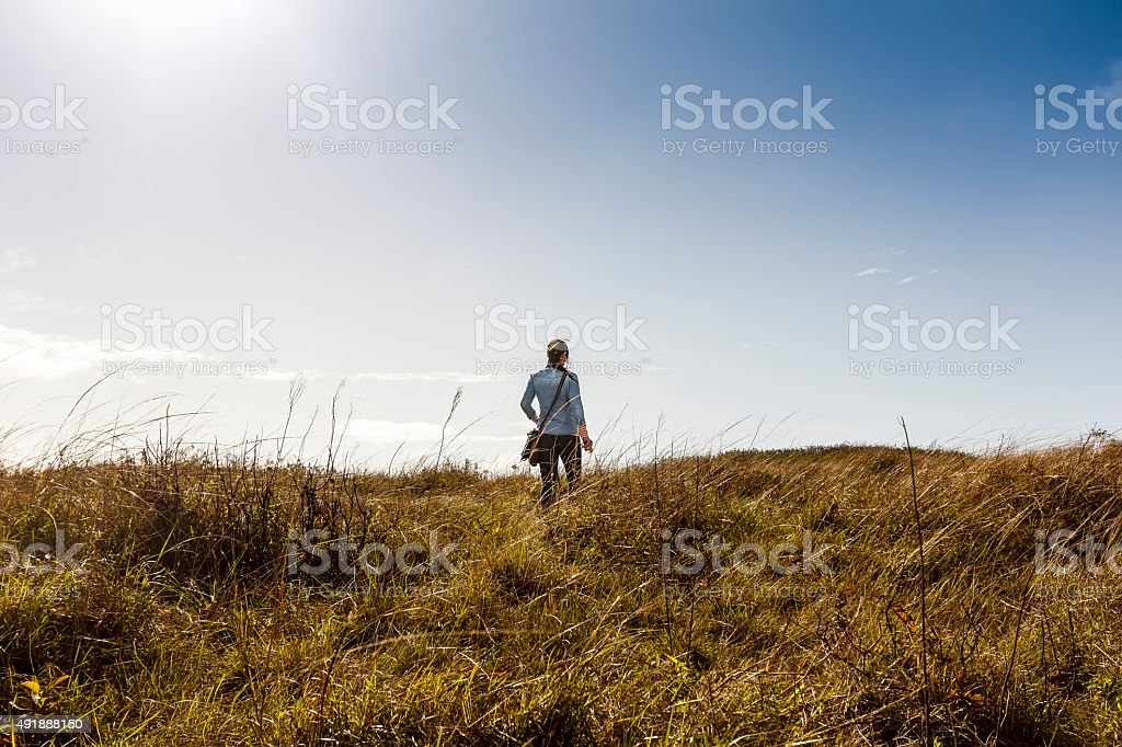 Woman Walking on Meadow on Sunny Morning stock photo