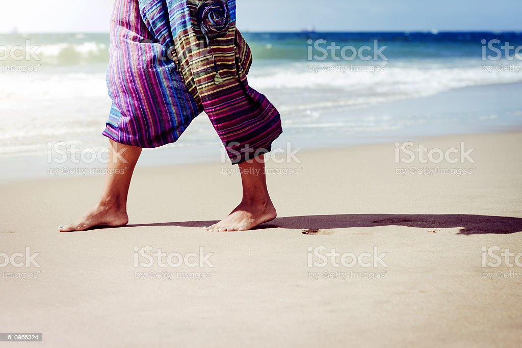 Woman walking on sand beach leaving footprints in the sand. stock photo