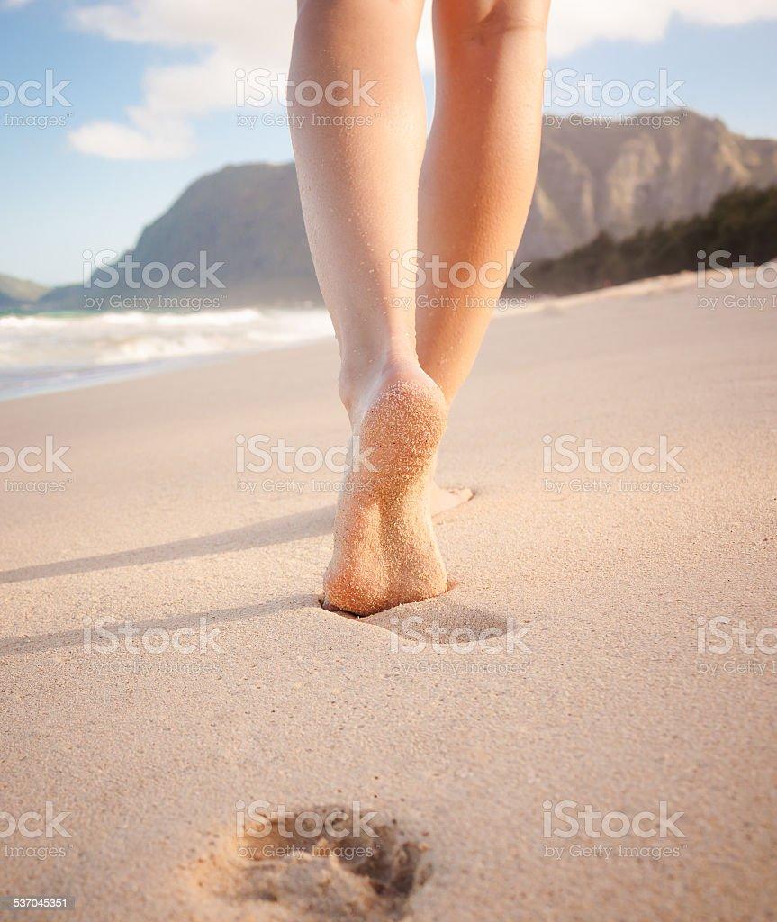 Woman walking on sandy beach stock photo