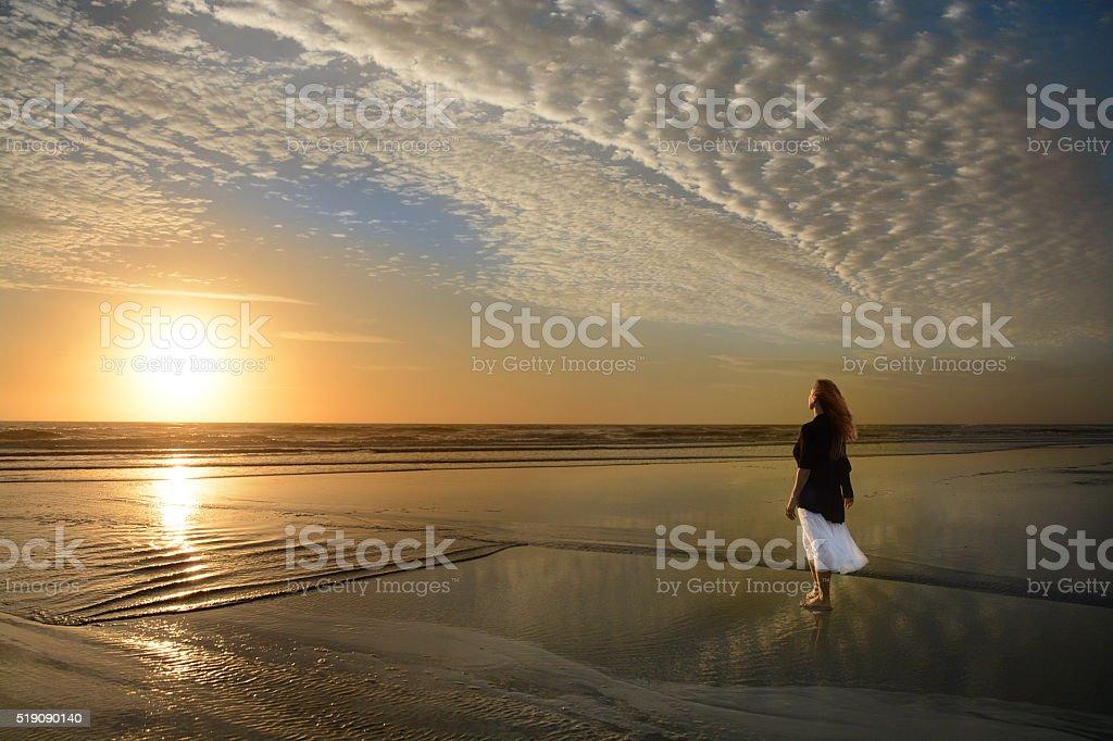 Woman walking on the beach at sunrise. stock photo