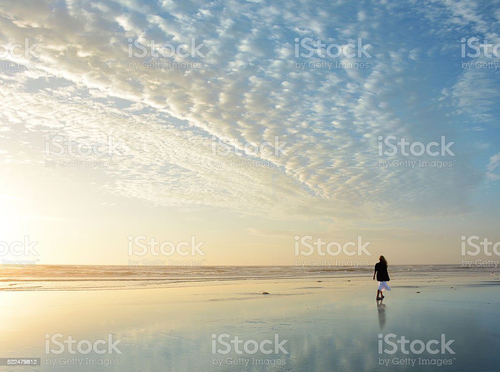 Woman walking on the beach at sunrise. stock photo
