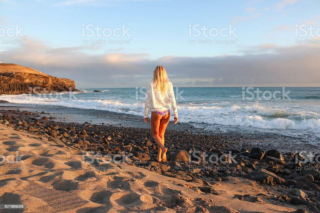 Woman walking on the beach at sunset stock photo