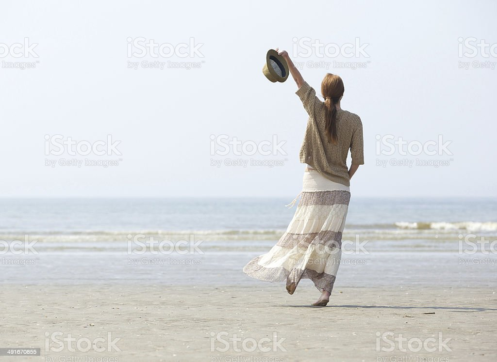 Woman walking on the beach with arm raised stock photo