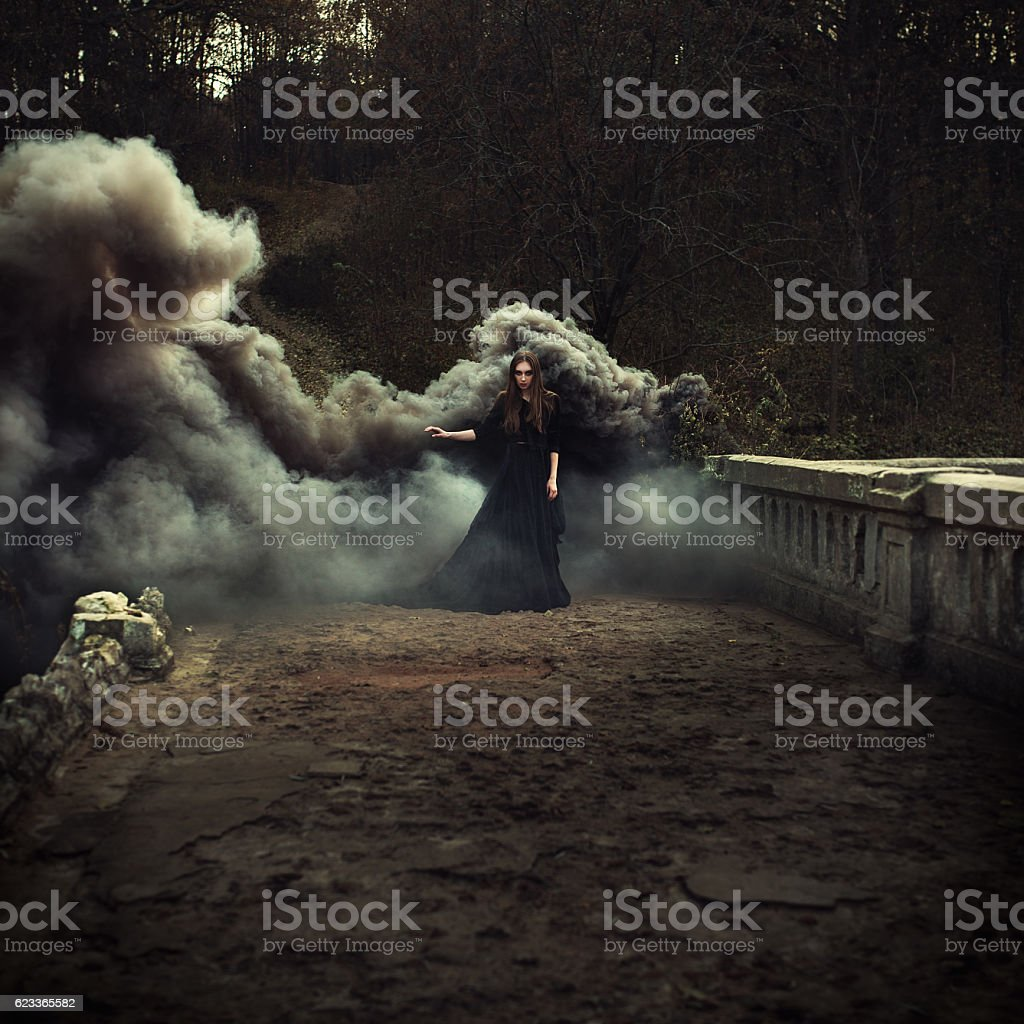 woman walking on the bridge in heavy black smoke stock photo