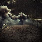 woman walking on the bridge in heavy black smoke