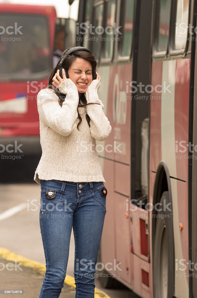 woman walking on the city street covering her ears concept stock photo