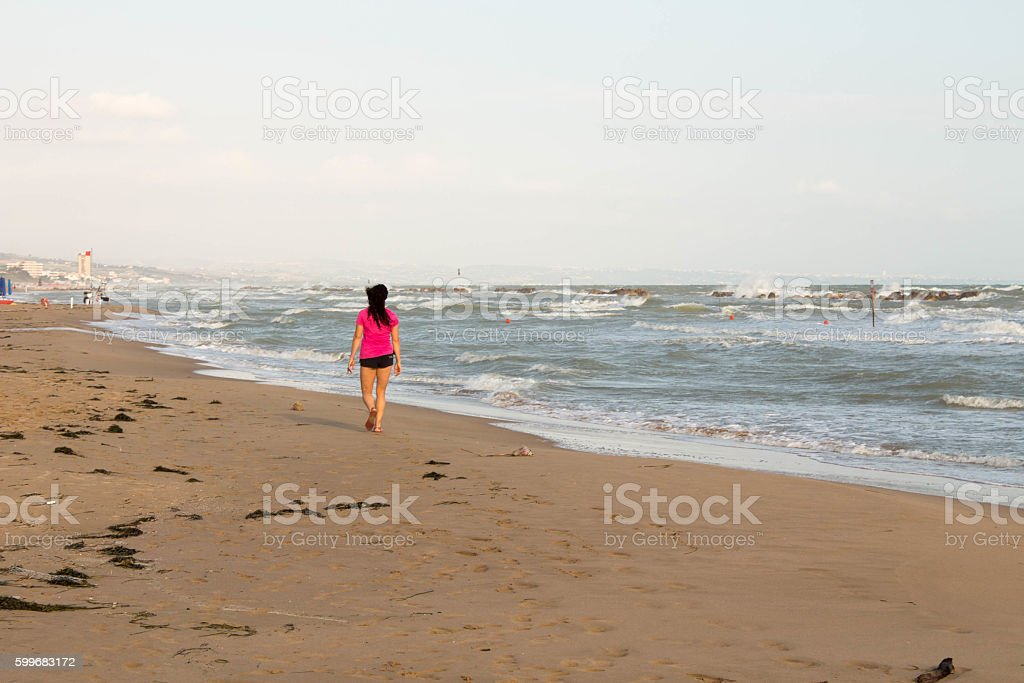 Woman walking on the foreshore in early morning stock photo