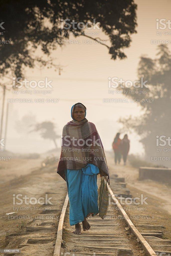Woman walking on the railway in misty morning stock photo