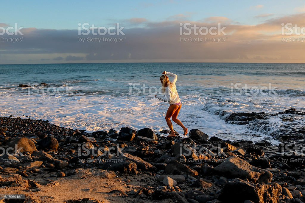 Woman walking on the rocks in sunset stock photo