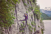 Woman walking on the rope in via ferrata, Gosausee, Austria