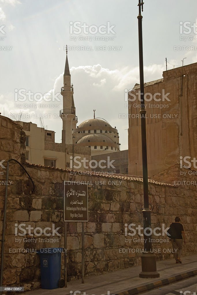Woman walking on the street behind a mosque, Jordan royalty-free stock photo