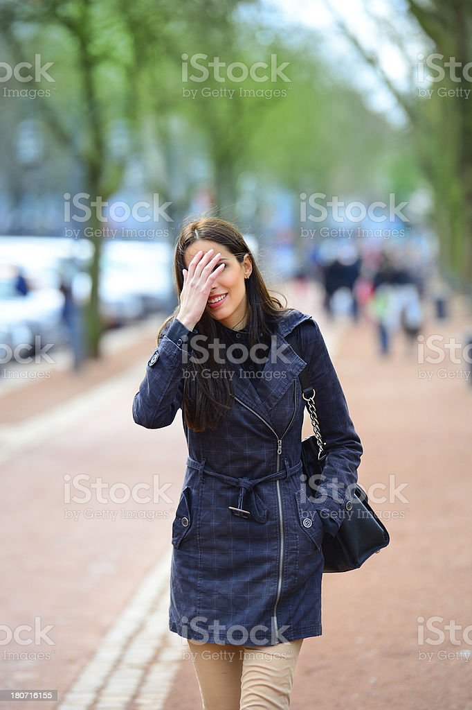 Woman walking on the street, park in background royalty-free stock photo