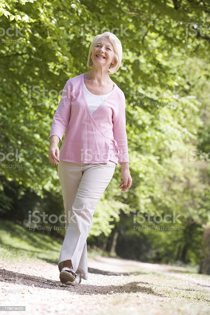 Woman walking outdoors smiling stock photo