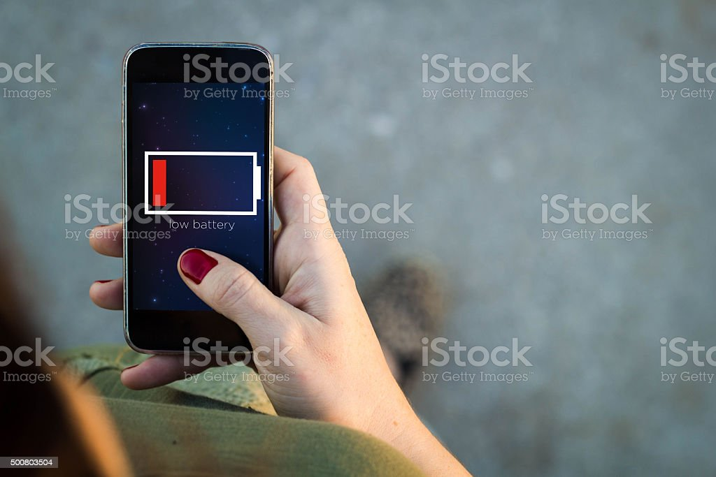 Woman walking smartphone low battery stock photo