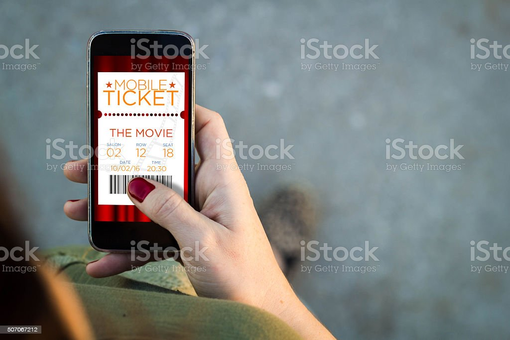 Woman walking smartphone with cinema digital tickets stock photo