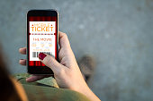 Woman walking smartphone with cinema digital tickets