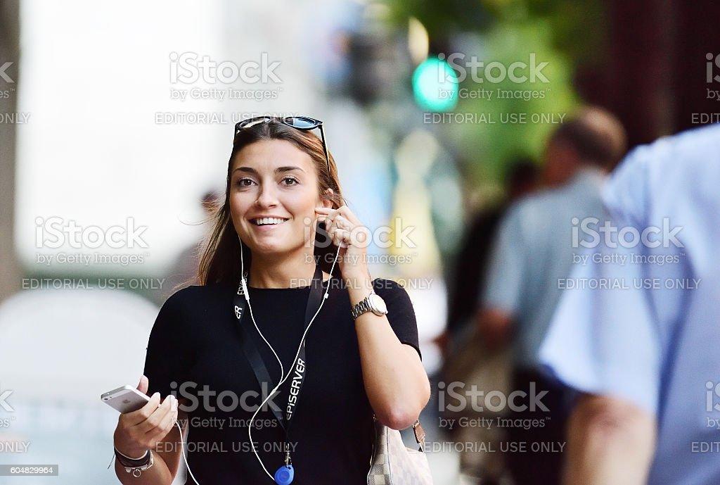 Woman, walking, talking, smiling, using mobile smart phone stock photo