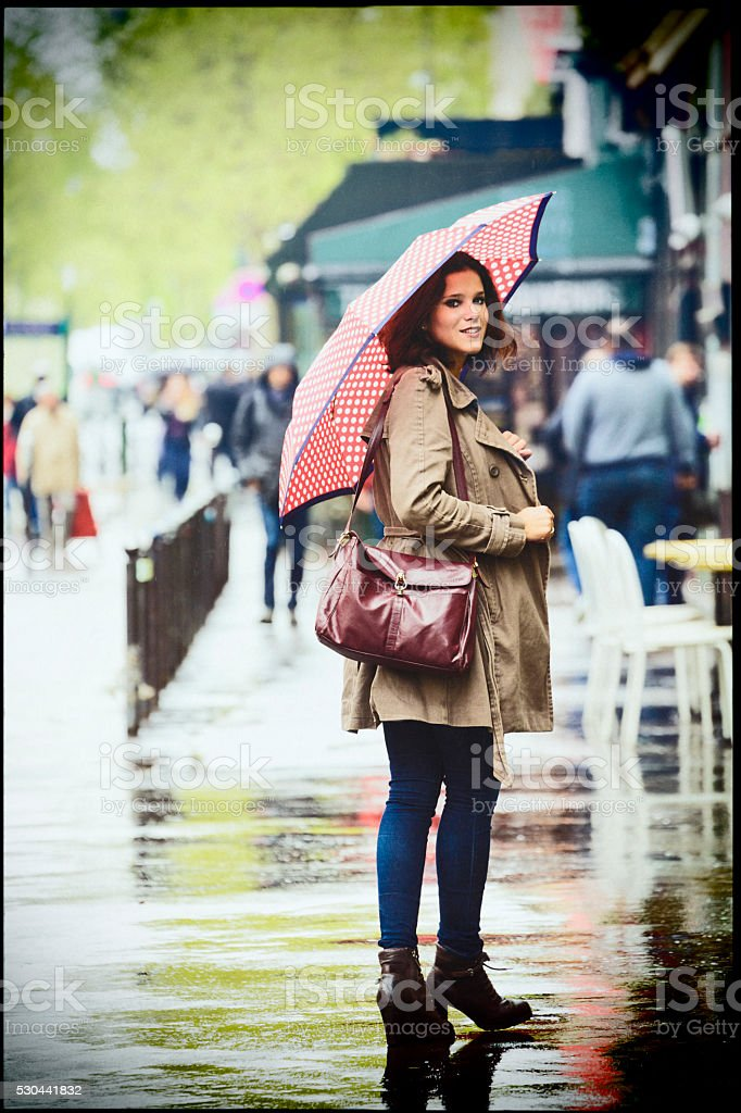 Woman walking the street on a rainy day in Paris. stock photo