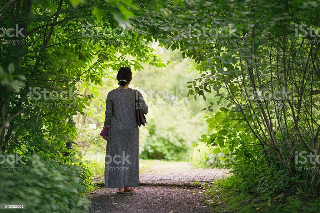 Woman walking through a green garden stock photo