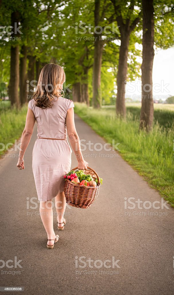 Woman walking through a park carrying a basket of vegetables stock photo