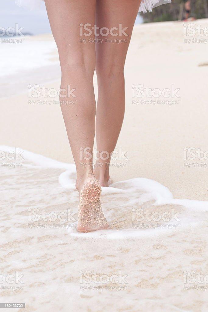 Woman walking through sand on the beach royalty-free stock photo